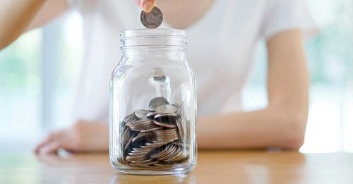Putting coins in a jar.